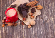 Cup of hot chocolate, cinnamon sticks, nuts and chocolate on wooden table on brown background Stock Image