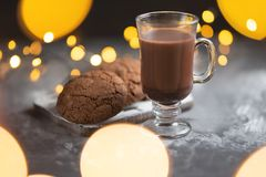 A cup of hot chocolate with chocolate cookies and lights royalty free stock photography