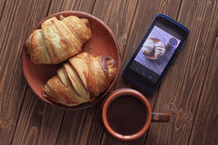 Cup of hot chocolate croissant on the plate and smartphone on a wooden table Stock Images
