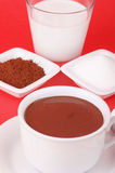 A cup of hot chocolate and its ingredients. Hot chocolate served in a white cup and the ingredients to prepared it: a glass of milk, cocoa powder and sugar Royalty Free Stock Images