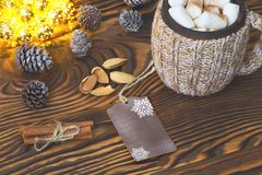 Cup of hot chocolate with marshmallows, nuts and cinnamon on a vintage wooden surface with christmas lights on background, selecti Stock Photos