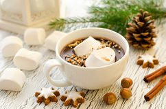 Cup of hot chocolate marshmallows and cinnamon christmas star co. Hot winter beverage with nuts on white wooden background Royalty Free Stock Photography