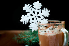 Cup of hot chocolate with marshmallows and decorative snowflake on the background of fir branches. Christmas card Stock Photography