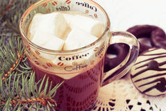 Cup of hot chocolate with marshmallows and decorative snowflake on the background of fir branches. Christmas card Stock Photo