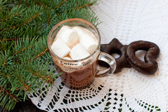 Cup of hot chocolate with marshmallows and decorative snowflake on the background of fir branches. Christmas card Stock Image