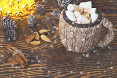 Cup of hot chocolate with marshmallows, nuts and cinnamon on a vintage wooden surface with christmas lights on background Royalty Free Stock Photos