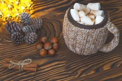Cup of hot chocolate with marshmallows, nuts and cinnamon on a vintage wooden surface with christmas lights on background, selecti Royalty Free Stock Images