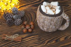 Cup of hot chocolate with marshmallows, nuts and cinnamon on a vintage wooden surface with christmas lights on background Stock Image