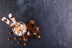 A cup of hot chocolate with marshmallows and sweets around royalty free stock photography
