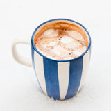 Cup of hot chocolate with melted marshmallows on snow Stock Image