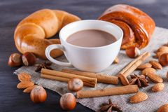 A cup of hot chocolate with nuts, buns and spices on black wooden background royalty free stock image