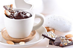 Cup of hot chocolate with pieces of chocolate and almond on ligh Stock Photography