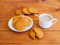 Cup of hot chocolate and plate of oat cookies on wooden table Royalty Free Stock Photos