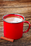 Cup of hot chocolate. Red mug with hot chocolate on wooden table royalty free stock photography
