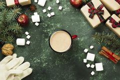 Cup of hot chocolate and various attributes of holiday on a gree. N background. Top view Stock Image