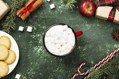 Cup of hot chocolate and various attributes of holiday on a gree. N background. Top view Royalty Free Stock Image