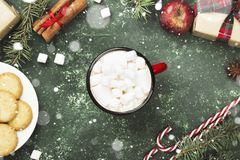 Cup of hot chocolate and various attributes of holiday on a gree. N background. Top view. Snow Royalty Free Stock Images