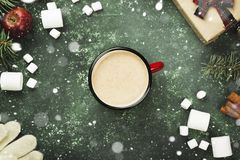 Cup of hot chocolate and various attributes of holiday on a gree. N background. Top view. Snow Royalty Free Stock Photos