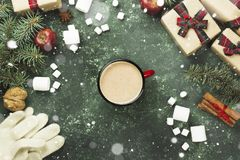 Cup of hot chocolate and various attributes of holiday on a gree. N background. Top view. Snow Stock Photography