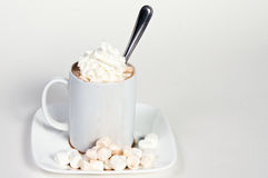 Cup of hot chocolate with whip cream and marshmallows. White cup of hot chocolate with whip cream, spilling over with marshmallows and a spoon on white Royalty Free Stock Photography