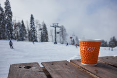 Cup of hot chocolate on wooden table over winter ski resort land Royalty Free Stock Photos