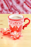 Cup of hot cocao with red poinsettia candle Stock Image