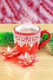 Cup of hot cocao with red poinsettia candle and Royalty Free Stock Photography