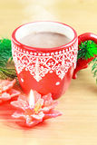 Cup of hot cocao with red poinsettia candle and Stock Photography