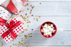 Cup of hot cocoa or chocolate with Christmas present on white wooden table Royalty Free Stock Images