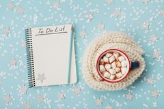 Cup of hot cocoa or chocolate with marshmallow and notebook with to do list on blue confetti background top view. Christmas plan. Royalty Free Stock Photography