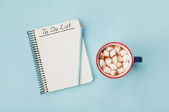 Cup of hot cocoa or chocolate with marshmallow and notebook with to do list on turquoise background top view. Christmas planning. Royalty Free Stock Images