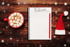 Cup of hot cocoa or chocolate with marshmallow, santa hat and notebook with to do list on table from above, christmas planning. Royalty Free Stock Photography