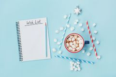 Cup of hot cocoa or chocolate, stylish fir tree and wish list on blue background top view. Christmas or new year concept. Flat lay Royalty Free Stock Photos