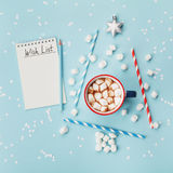 Cup of hot cocoa or chocolate, stylish fir tree and wish list on turquoise confetti background top view. Christmas concept. Cup of hot cocoa or chocolate Stock Image