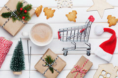 Cup of hot cocoa, holiday decorations, gift, present, fir tree and shopping basket on white table from above. Christmas planning. Royalty Free Stock Image