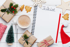Cup of hot cocoa, holiday decorations, gift, present, miniature fir tree and notebook with Christmas to do list on white table. Royalty Free Stock Image