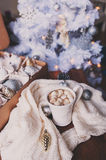 Cup of hot cocoa with marshmallow with Christmas decorations at home, Christmas tree on background Royalty Free Stock Photo