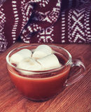 Cup of hot cocoa with marshmallow and warm knitted scarf on wood Royalty Free Stock Photo