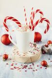 Cup of hot cocoa with marshmallows and candy canes on blue rustic background. With Christmas lights of bokeh Royalty Free Stock Photos