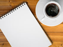 Cup of hot coffe. White cup of hot coffee and white sketch book on wood table Royalty Free Stock Photo