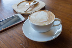 Cup of hot coffee ad smartphone put on old wooden table backgrou. Nd.Copy space stock photo