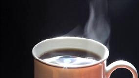 Cup of hot coffee against black background, texture stock video