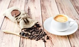 Cup of hot coffee and coffee beans in a wooden scoop and spilling out from a hessian bag on wooden rustic table. Close-up royalty free stock image