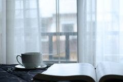 A cup of hot coffee in bed with nice view and white curtain from window. stock photo