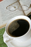 Cup of hot coffee, book in background Royalty Free Stock Images