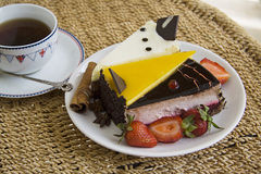 Cup of hot coffee and cakes on plate Royalty Free Stock Image
