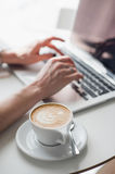 Cup of hot coffee or cappuccino with a pattern. Blurred hands are typing on keyboard of a laptop in the background. Cup of hot coffee or cappuccino with a Royalty Free Stock Photography