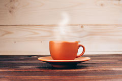 Cup of hot coffee. Ceramic orange cup of fresh hot coffee with foam, standing on wooden table on wooden background Stock Photo