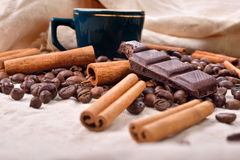 Cup of hot coffee with cinnamon sticks, bitten bar of chocolate Stock Image
