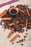 Cup of hot coffee with cinnamon sticks, bitten bar of chocolate Stock Photo